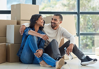 A couple sitting on the floor, leaning up against a pile of moving boxes
