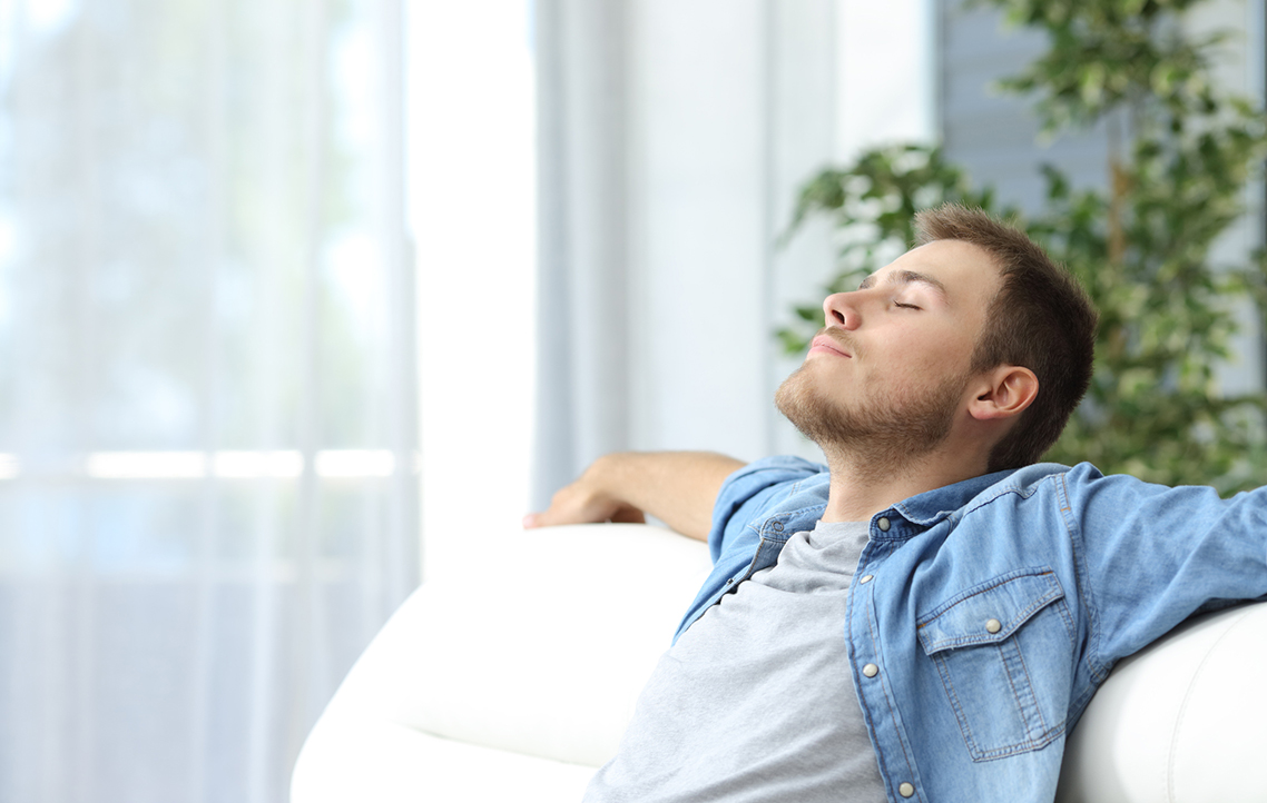 A relaxed man reclining on the couch