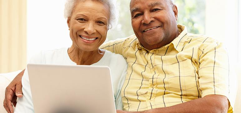 Elderly couple set up automatic bill pay online through their laptop.