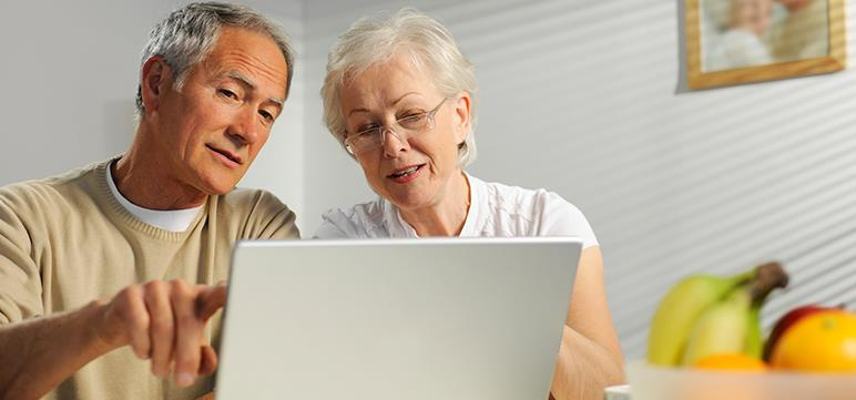 Retired couple viewing online account information on a laptop