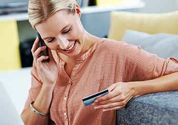 A woman talking on the phone and holding and looking at a credit card