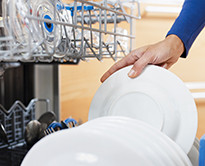 A person putting a plate into a dishwasher