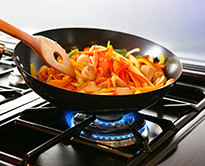 A closeup of vegetables being stirred in a pan atop a burner on a gas stove