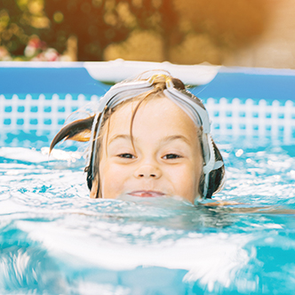 A closeup of a child's face as she swims in a backyard pool
