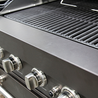 A closeup of the grates and dial on a gas grill