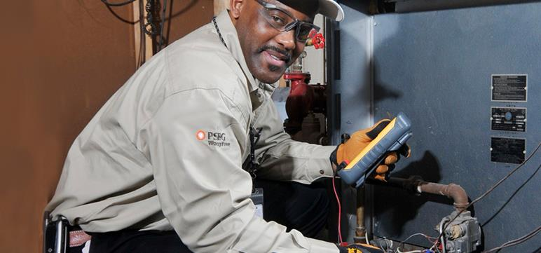 A PSE&G technician fixes a customer's heating system.